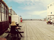 People Sitting At Table On North Pier Against Cloudy Sky