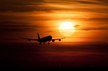 Silhouette Airplane Flying Against Orange Sky