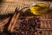 Natural High Quality Arabica Coffee Beans, Honey, Cinnamon And Star Anise On A Bamboo Napkin In The Sunlight