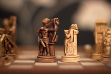 Close-up Of Antique Chess Pieces On Board