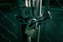 Locked Gate Tethered By Metal Chain And Old Rusty Padlock On Dark Background.