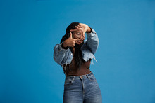 Happy Black Female With Braids In Denim Jacket Smiling And Looking At Camera While Framing Face With Hands Against Blue Background