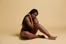 Curvy Beautiful African American Woman With Braids In Lingerie Looking At Camera Sitting On The Floor Against Yellow Background