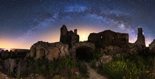 Aged Ruined Building Among Green Field Plants Under Colorful Starry Night Sky With Milky Way