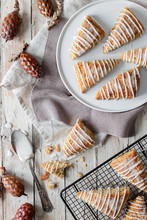 Top View Of Tasty Sweet Homemade Triangle Scones Decorated With Sugar Icing Placed On White Plate And On Metal Grid On Wooden Table With Decorative Tree Cones