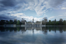 Architectural Ensemble Of Monument To Alfonso XII On Waterfront Of Calm Quiet Pond In Park