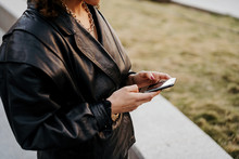 Young Businesswoman In Retro Black Leather Jacket And Skirt Browsing Smartphone While Standing In Arched Passage In Park Before Work