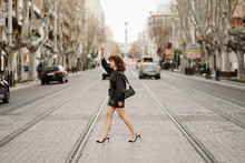 Side View Of Successful Businesswoman In Retro Leather Suit Waving Hand And Trying To Catch Taxi While Crossing Tram Rails On City Street