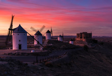 Ancient Windmills And Aged Castle Against Bright Sunset Sky In Evening In Countryside