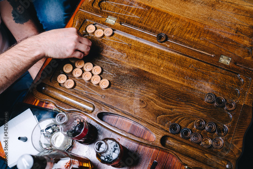 Photo Men are playing backgammon in a bub, directly above view