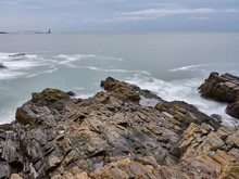 A Rocky  Granite Ledge On Casco Bay In Maine With The Rams Ledge Lighthouse In The Background
