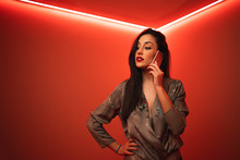 From Below Trendy Woman Using Smartphone While Standing With Hand On Hip Looking Away In Room With Bright Red Neon Illumination At Night Club