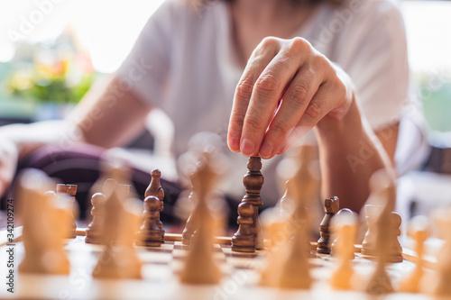 Obraz na plátně Pensive woman plays chess