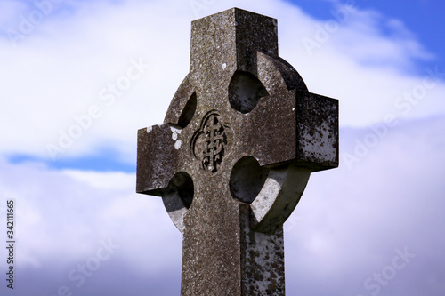 Celtic cross in an Irish cemetery with blue sky Wallpaper Mural