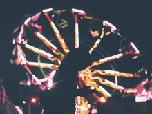 Side View Of Silhouette Woman Using Smart Phone While Standing Against Illuminated Ferris Wheel At Night