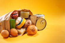 Various Groceries Inside Paper Bag On Top Of Yellow Background, With Available Copy Space. Stockpiling Food Concept.