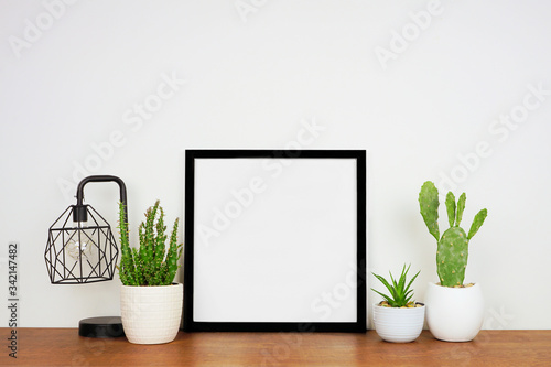 Fototapeta Mock up black square frame with home decor and potted plants. Wood shelf and wall. Copy space. obraz