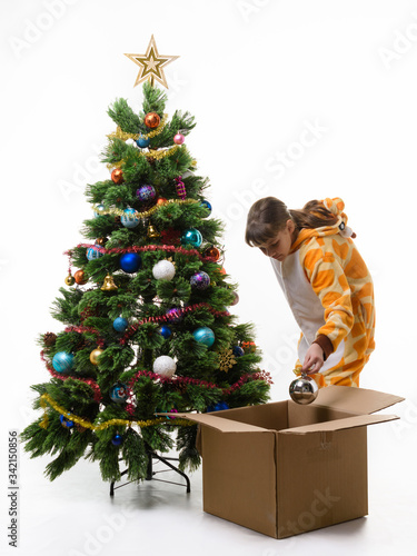 Photo Girl puts Christmas decorations in a storage box