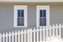Two Double-hung Windows On A Grey Exterior Wall Of A Vintage Style Building. The Building Has Narrow Clapboard On The Wall. There's A White Picket Fence In The Foreground With A Mound Of White Snow.