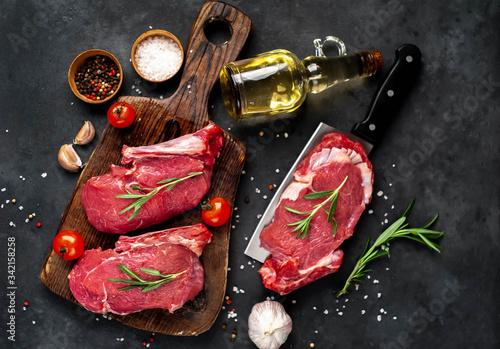 Fototapeta raw three beef steaks on a cutting board with spices on a stone background obraz na płótnie