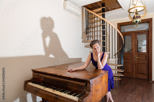 Photo Wooden old-fashioned forte piano with young girl woman pianist looking at camera
