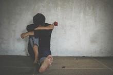 Sad Man Holding Rose Sitting Against Wall