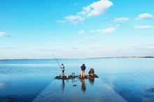 Men Fishing At Pier Against Sea