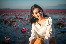 Portrait Of Young Woman Smiling While Sitting Against Water Lilies In Pond