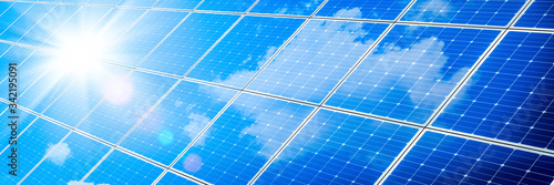 Fototapeta Array Of Solar Panels With Blue Sky And Sunlight Reflection- Clean Energy Concept obraz