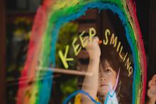 """虹とユニコーンの絵と""""KEEP SMILING""""の文字を描く少女"""