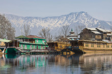 Houseboats On Dal Lake In Srinagar, Summer Capital Of Jammu And Kashmir With Himalayan Mountains In Background