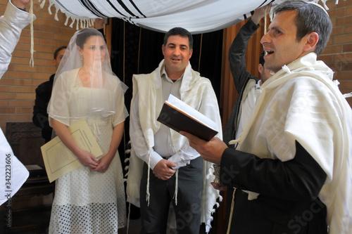 Obraz na płótnie Rabbi blessing Jewish bride and a bridegroom in Jewish wedding ceremony