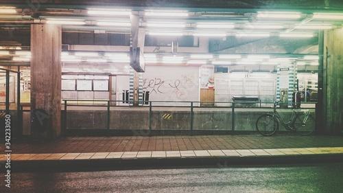 Fototapety, obrazy: Bicycle Parked On Sidewalk At Illuminated Bus Station