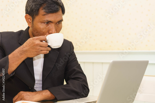 Fotografie, Obraz Middle aged boss is sipping morning coffee while using laptop in the home