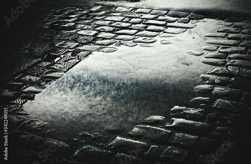 Fotografia Puddle In Cobblestone Paving