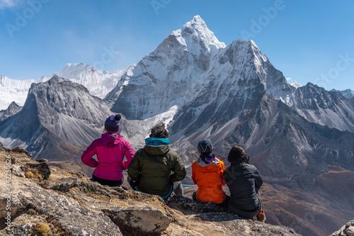 Photo Trekkers sitting on rock and looking to Ama Dablam mountain peak at Nangkart Sha