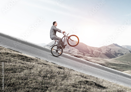 Photo Businessman riding downhill by bike