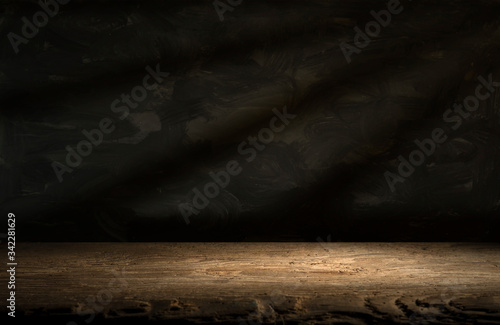 Old wood table with blurred concrete block wall in dark room background Wallpaper Mural