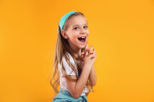 Surprised Little Child Girl In Summer Clothes On A Colored Yellow Background. Vacation Concept