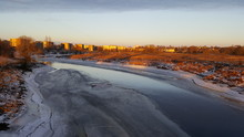 Frozen River In City Against Sky During Winter
