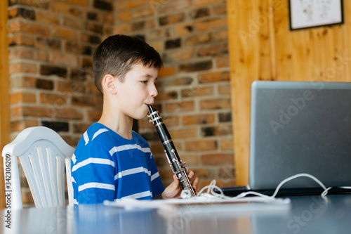Foto Boy with a clarinet plays music. Online music lesson concept