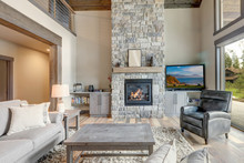 Living Room Luxury Interior With Large Stone Fireplace And Leather Furniture And Huge Tall Windows With Natural Tones With TV.