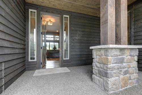 Fototapeta Grey new beautiful rustic home front door and entrance exterior with open door and lights on. obraz