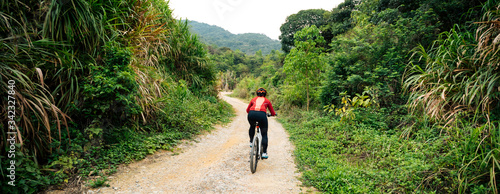 Fotomural Woman cyclist riding a bike on a nature trail in the mountains