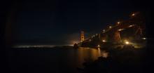 Illuminated Golden Gate Bridge Over Bay At Night