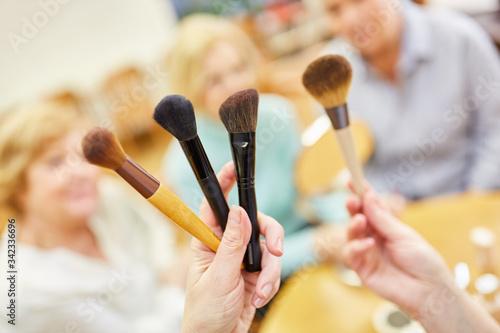 Fototapeta Visagist zeigt Schminkpinsel für das altersgerechte Make-Up im Senioren Schminkkurs obraz na płótnie