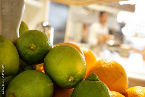 Stampa su Tela Lime in primo piano e dietro arance dentro un mercato