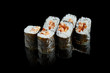 Traditional japanese maki sushi rolls with eel on a black background with reflection. Photo for the menu. Close up
