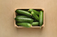 Box With Green Cucumbers On Color Background