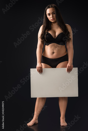 Photo Front view of full length plus size girl with empty board on black background